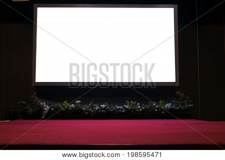 Projector Screen On Stage With Red Carpet In Conference Hall.
