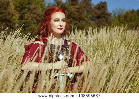 In the tall grass there is a woman with a sword a close-up portrait.