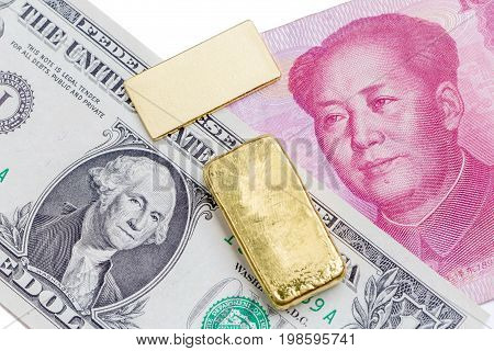 Gold bar over the US dollar bill and Chinese yuan banknote on white background economy finance concept.