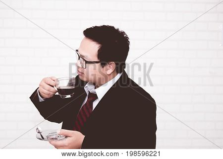 business man drinking coffee in his office alone
