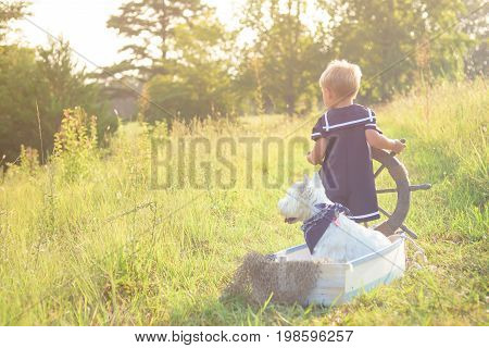 Boy in sailor suit playing with best friend - white dog - in the boat, pretending to sail across summer sea of grass. Adventure, children activity, game.