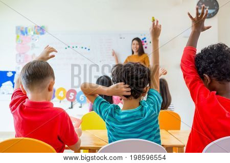 Preschool kid raise arm up to answer teacher question on whiteboard in classroomKindergarten education concept.