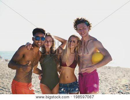 Group of happy friends playing at beach volley at the beach