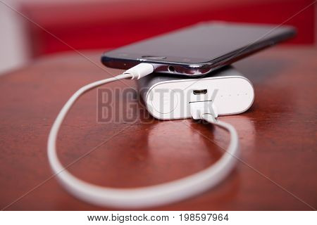 Mobile Phone Charging With Power Bank and USB cord, on wooden table