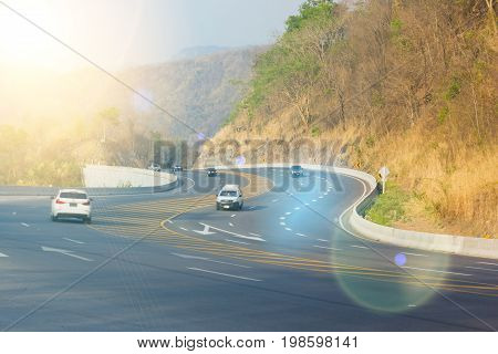 CHIANG RAI THAILAND - FEBRUARY 20 : Curve asphalt highway in the mountain with vehicles in the evening with lens flare on February 20 2016 in Chiang rai Thailand.