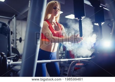Close-up of a girl clapping hands before starting a workout with a barbell. Concept fitness, weightlifting. copyspace
