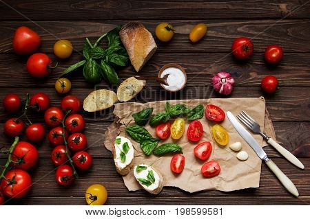 Italian Bruschetta with cheese basil and tomatoes. Cooking. Ingredients for cooking bruschetta and salad. Top view.