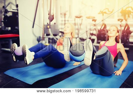 Girls are engaged in fitness with medical ball sports shot in the gym. Concept of team training with coach, mentor.