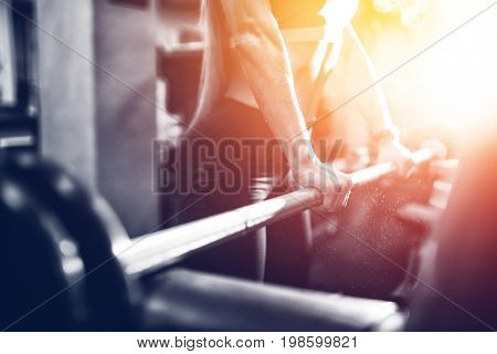Close-up of a girl holding her hands with a barbell for pulling, squatting, fitness in the gym. Concept sports, toned picture, copyspace for text. Glare of sun and light.