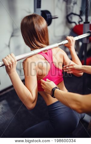 coach helps the girl to perform the exercise squat with the bar in the gym. Concept fitness, team sports.