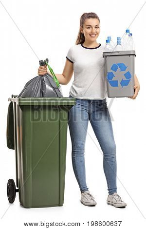 Full length portrait of a young girl with a recycling bin and a garbage bag next to a trash can isolated on white background
