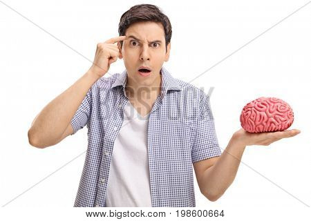 Young man with a brain model holding a finger on his temple asking do you have a brain isolated on white background