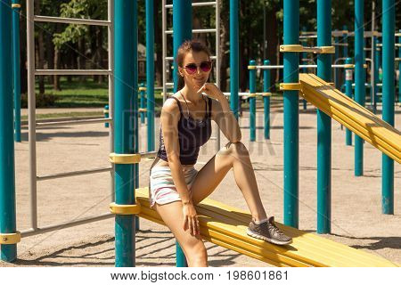 Cutie cheerful girl in sunglasses smiling on a playground outdoors