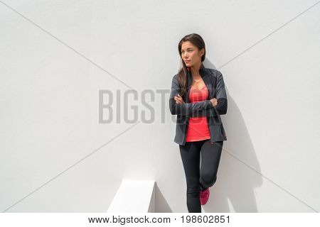 Activewear Asian girl model woman leaning on wall in yoga leggings and running jacket ready to train at gym. Active lifestyle healthy people.