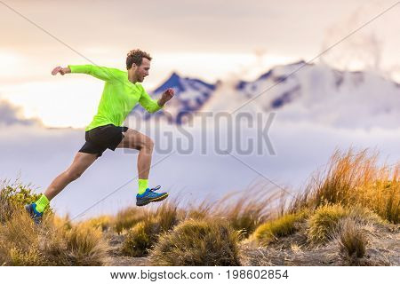 Trail runner man running on New Zealand mountains nature. Sport athlete jumping over hills with mountain trail at dusk landscape background . Active health and motivation lifestyle