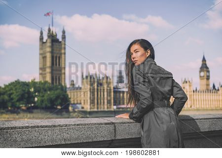 London trench coat business woman at Westminster. Fashion businesswoman in grey raincoat. Asian beauty model outdoor.