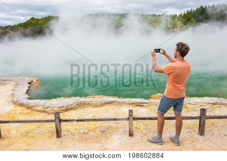 New Zealand travel tourist taking phone picture of famous attraction Champagne pool, Waiotapu. Active geothermal area, Okataina Volcanic Centre, Reporoa, in Taupo Volcanic Zone, Rotorua, north island.