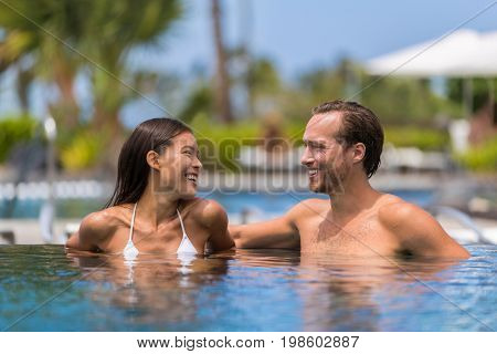 Happy swimming pool couple having fun laughing talking on luxury resort hotel travel holiday together on summer vacation. Asian woman, caucasian man in love on honeymoon.