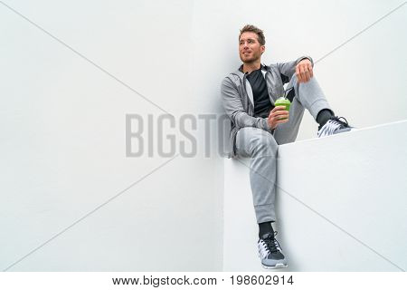 Healthy sport man drinking green smoothie during training at gym in activewear sweatpants outdoor. Athlete sitting relaxing post-workout.
