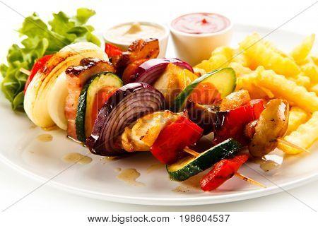 Shashlik - grilled meat and vegetables on white background