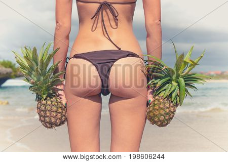 Sexy tropical woman butt close up with exotic pineapple fruit on the beach of paradise island of Bali. Healthy diet concept.