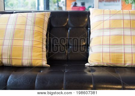 Yellow Pillow And Brown Leather Sofa Near Window At Restaurant Or Cafe