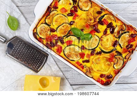 delicious zucchini casserole with red bell pepper red bean ham and cheese in gratin dish on old wooden table with piece of cheese grater on papel view from above close-up