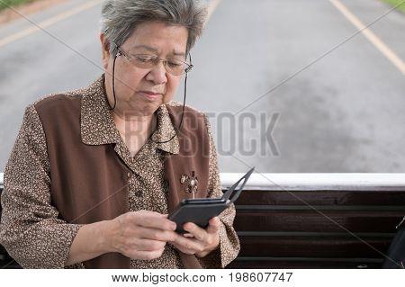 Asian Elder Woman Holding Mobile Smart Phone On Bus. Elderly Senior Female Texting Message, Using Ap