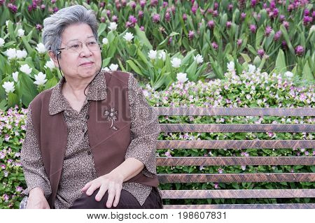 Asian Elder Woman Sitting On Bench In Garden. Elderly Senior Female Resting And Relaxing In Park