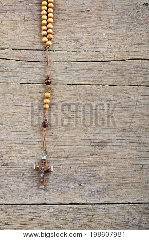 Rosary beads on the old wooden table