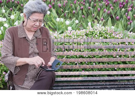 Asian Elder Woman Holding Mobile Smart Phone While Sitting On Bench In Garden. Elderly Senior Female