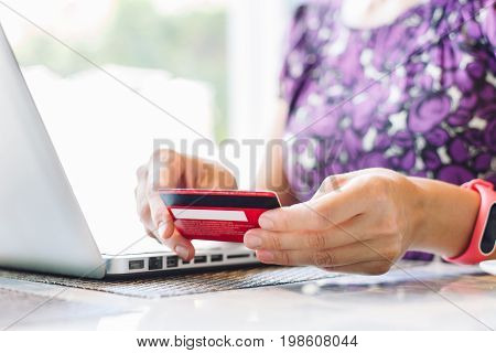Anonymous woman pays for credit card purchases through the Internet sitting in indoor cafe with laptop.