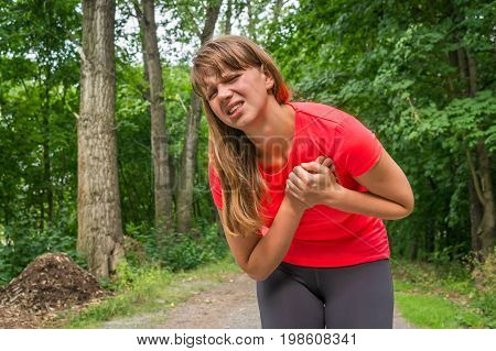 Woman is having heart attack during running activity in park
