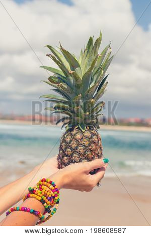 Woman hand with fresh exotic pineapple fruit on the ocean background. Fresh healthy diet food concept. Bali island.