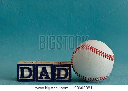 Dad spelled with colorful blocks with a baseball