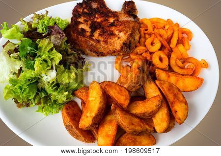 Pork chop in breadcrumbs served with roasted potato lettuce and lettuce on a white plate.