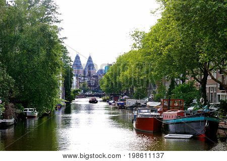 Amsterdam Holland Europe - scenic day view of the canal boats and trees