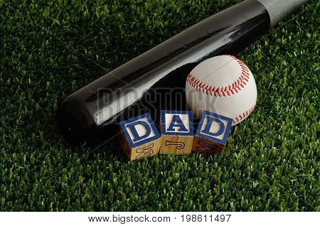 Dad spelled with colorful blocks with a baseball and a bat