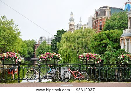 Amsterdam Holland Europe - bicycles and flowers over a bridge