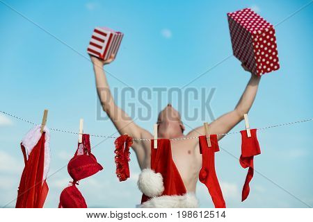 New year guy with muscular body on blue sky. Laundry and dry cleaning. Santa claus man hanging clothes for drying. Xmas red costume on rope with pin. Christmas man with happy face hold present box.