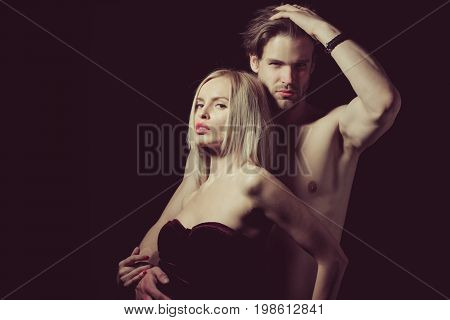 Love and romance. Relations of girl and guy. Couple in love of sexy man and woman. Boyfriend and girlfriend on black. Man with muscular body with sexy girl copy space