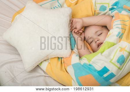 Small baby dreaming. Childhood and happiness. Child sleep in bed. Trust and tenderness. Sleepy baby in colorful blanket and star pillow.