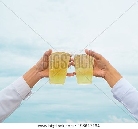 Celebration party hands hold beverage beers with plastic glasses and cheer for success have beautiful sky as background