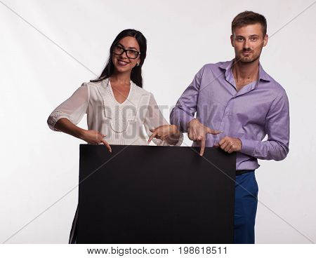 Young confident woman portrait of a confident businesswoman showing presentation, pointing placard gray background. Ideal for banners, registration forms, presentation, landings, presenting concept.