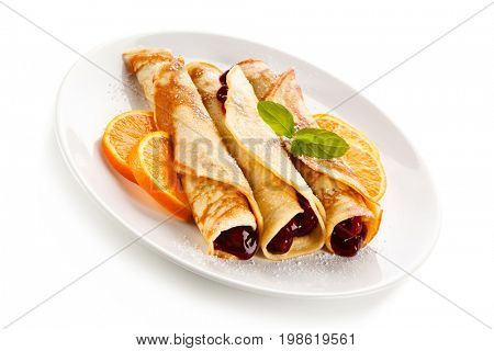 Crepes with cherries and cream on white background