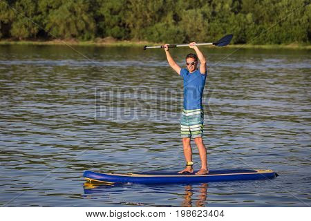Young sportsman standing on paddle board in nature