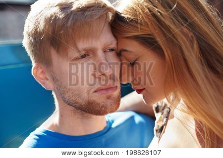 Close up shot of handsome guy with stubble and fair hair having sad look his beautiful girlfriend or wife burrying her face into his cheek. Young couple saying goodbye. People and relationships