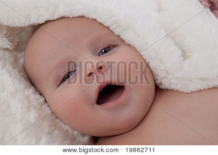 Adorable Baby Boy Lying On Fur Blanket Smiling