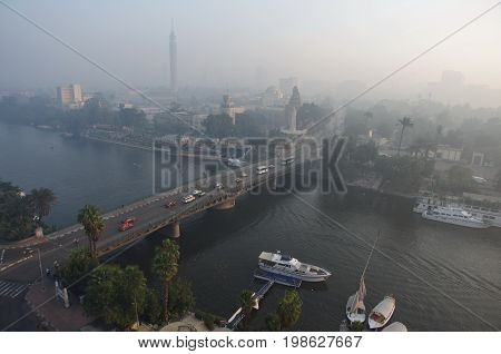 Panorama of morning Cairo, overlooking the Nile. Light haze, Egypt. Cold colors. City life - people, canoeists, yachts, cars, public transport. Landscape