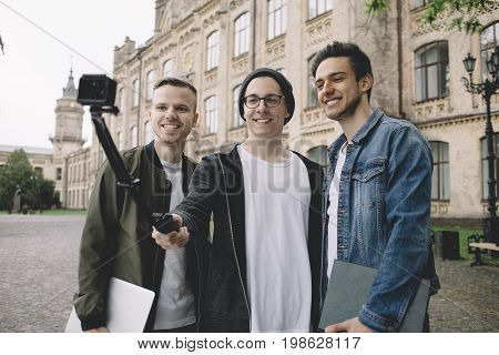 Three handsome guys are standing outside near university where they study. Young men are taking selfies and posing at camera. Close up